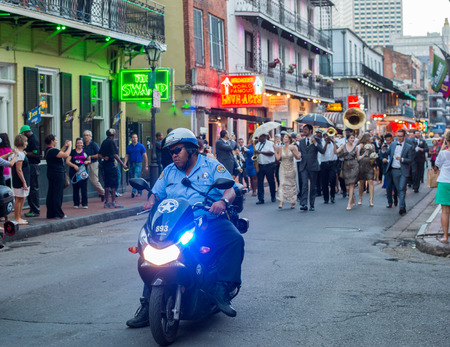 bourbon street: New Orleans, LA, USA - October 9, 2014: Police escort an early evening parade on Bourbon Street in New Orleans. Bourbon Street is the liveliest street in the French Quarter of New Orleans. Editorial