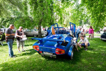 annually: Norrkoping, Sweden - June 6, 2014: Antique cars at show in the Olai Park during National day celebrations in Norrkoping. The national day of Sweden is celebrated on June 6 annually and is an official holiday.