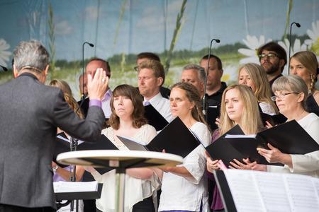 persona cantando: Norrk�ping, Suecia - 6 de junio 2014: El coro Bel Canto entretiene durante las celebraciones del d�a nacional en Norrk�ping. El d�a nacional de Suecia es un d�a de fiesta oficial.