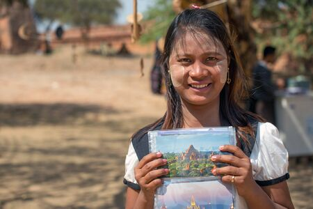 post cards: Bagan, Myanmar - February 8, 2014: Young Burmese woman sells post cards in Bagan. Facial painting with white-yellow color called Thanaka is a popular cosmetic in Myanmar.