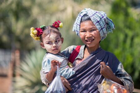 facial painting: Bagan, Myanmar - February 8, 2014: Burmese betel chewing woman with child. Facial painting with white-yellow color called Thanaka is a popular cosmetic in Myanmar. Editorial