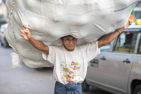 Yangon, Myanmar - February 10, 2014: Burmese worker carrying a huge load in Chinatown. Myanmar is ethnically diverse with 51 million inhabitants belonging to 135 ethnic groups.
