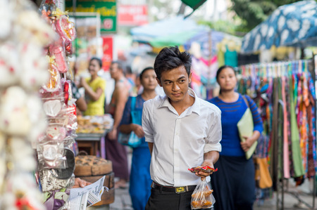 ethnically diverse: Yangon, Myanmar - February 10, 2014: Burmese man walking in Chinatown. Myanmar is ethnically diverse with 51 million inhabitants belonging to 135 ethnic groups.