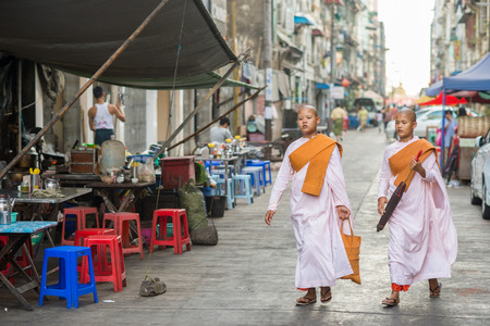 ethnically diverse: Yangon, Myanmar - February 10, 2014: Burmese Buddhist nuns walking in Chinatown. Myanmar is ethnically diverse with 51 million inhabitants belonging to 135 ethnic groups. Editorial