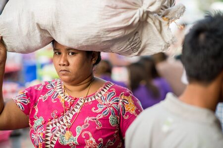 ethnically diverse: Yangon, Myanmar - February 10, 2014: Burmese woman carrying a heavy load on her head in Chinatown. Myanmar is ethnically diverse with 51 million inhabitants belonging to 135 ethnic groups.