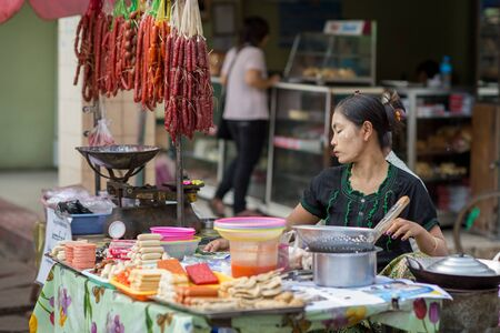 ethnically diverse: Yangon, Myanmar - February 10, 2014: Burmese woman cooking street food in Chinatown. Myanmar is ethnically diverse with 51 million inhabitants belonging to 135 ethnic groups. Editorial
