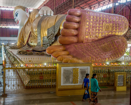 Yangon, Myanmar - February 10, 2014: Burmese women walk past the feet of the reclining Buddha at Chauk Hhat Gyi Pagoda. The Buddha is 65 meters long.
