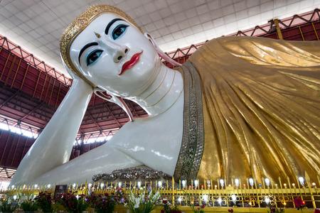 enormous: Yangon, Myanmar - February 10, 2014: The enormous reclining Buddha at Chauk Hhat Gyi Pagoda. The Buddha is 65 meters long.