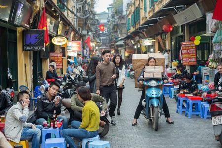 하노이, 베트남 - 2015 년 2 월 15 일 : 베트남 여성이 하노이 구시 가지에있는 오토바이로 상자를 운송합니다.