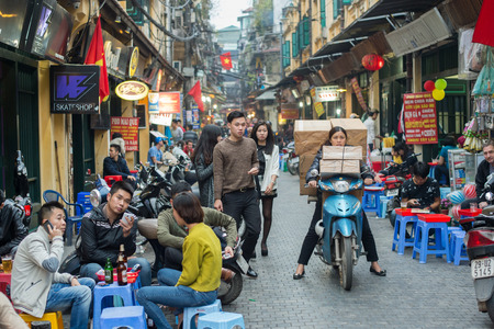 Hanoi, Vietnam - February 15, 2015: Vietnamese woman transports boxes on a motorbike in the old quarter of Hanoi.