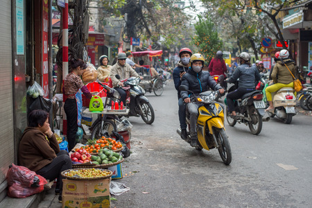 approximately: Hanoi, Vietnam - February 15, 2015: Busy traffic in the old quarter of Hanoi. There are approximately four million motorbikes on the streets of Hanoi.
