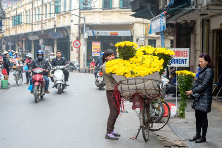 guilds: Hanoi, Vietnam - February 10, 2015: Flower shop on wheels in the old quarter of Hanoi. The 36 old streets and guilds of the old quarter are a major tourist attraction displaying everyday life of Hanoi