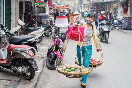 Hanoi, Vietnam - February 10, 2015:  Vietnamese woman selling fruits from two baskets hanging on a carrying pole in the old quarter of Hanoi. The 36 old streets and guilds of the old quarter are a major tourist attraction. Editorial