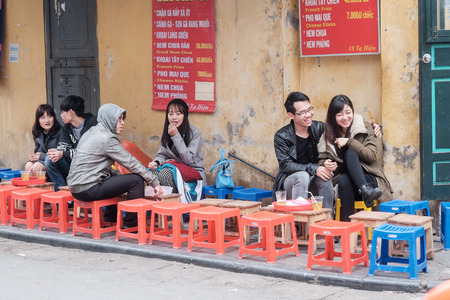 guilds: Hanoi, Vietnam - February 15, 2015:  Young Vietnamese people at an outdoor restaurant in the old quarter of Hanoi. The 36 old streets and guilds of the old quarter are a major tourist attraction. Editorial