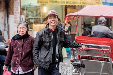 Hanoi, Vietnam - 10 februari 2015: bestuurder van de riksja wacht op klanten in de oude wijk van Hanoi. De 36 oude straten en gilden van de oude wijk zijn een belangrijke toeristische attractie.