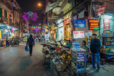 Hanoi, Vietnam - February 11, 2015: Street scene by night in the old quarter of Hanoi. The 36 old streets and guilds of the old quarter are a major tourist attraction. Editorial