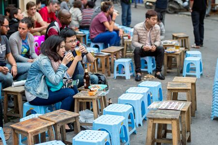guilds: Hanoi, Vietnam - February 15, 2015:  Vietnamese people and tourists at an outdoor restaurant in the old quarter of Hanoi. The 36 old streets and guilds of the old quarter are a major tourist attraction.