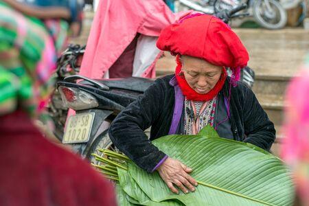 diversidad cultural: Sapa, Vietnam - 13 de febrero 2015: Mujer Red Dao vender dong hojea en un mercado de Sapa. Sapa es famoso por su paisaje accidentado y su rica diversidad cultural. Gente Dao Rojo es una de las muchas tribus de colores. Editorial