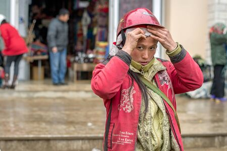 cultural diversity: Sapa, Vietnam - February 13, 2015: Red Dao woman at a market in Sapa. Sapa is famous for its rugged scenery and its rich cultural diversity. Red Dao people is one of many  colorful tribes. Editorial