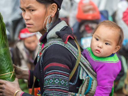 cultural diversity: Sapa, Vietnam - February 13, 2015: Hmong woman with child at a market in Sapa. Sapa is famous for its rugged scenery and its rich cultural diversity. Hmong people is one of many  colorful tribes.
