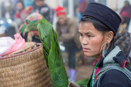 cultural diversity: Sapa, Vietnam - February 13, 2015: Hmong woman at a market in Sapa. Sapa is famous for its rugged scenery and its rich cultural diversity. Hmong people is one of many  colorful tribes. Editorial