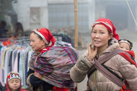 cultural diversity: Sapa, Vietnam - February 13, 2015: Red Dao women with children in a village outside Sapa. Sapa is famous for its rugged scenery and its rich cultural diversity. Red Dao people is one of many a colorful tribes. Editorial