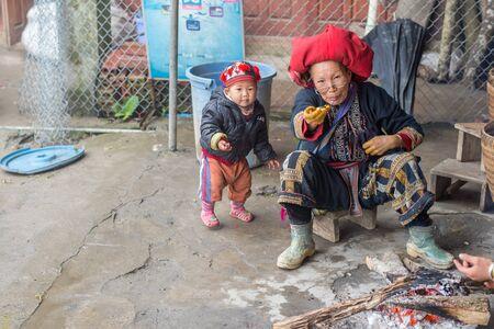 diversidad cultural: Sapa, Vietnam - 13 de febrero 2015: Mujer Red Dao con un nieto en un pueblo fuera de Sapa. Sapa es famosa por su paisaje agreste y su rica diversidad cultural. La gente de Red Dao es una de las muchas tribus y coloridos.