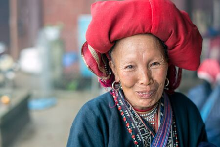 cultural diversity: Sapa, Vietnam - February 13, 2015: Red Dao woman in a village outside Sapa. Sapa is famous for its rugged scenery and its rich cultural diversity. Red Dao people is one of many a colorful tribes.