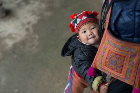 cultural diversity: Sapa, Vietnam - February 13, 2015: Red Dao child in a village outside Sapa. Sapa is famous for its rugged scenery and its rich cultural diversity. Red Dao people is one of many a colorful tribes.