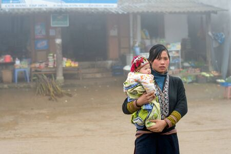 diversidad cultural: Sapa, Vietnam - 13 de febrero 2015: Red Dao mujer lleva un ni�o en un pueblo fuera de Sapa. Sapa es famoso por su paisaje accidentado y su rica diversidad cultural. Gente Dao Rojo es una de las muchas tribus y coloridos.