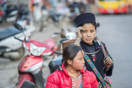 diversidad cultural: Sapa, Vietnam - 15 de febrero 2015: mujer de Hmong en una calle de Sapa. Sapa es famoso por su paisaje accidentado y su rica diversidad cultural. Hmong es una de las muchas tribus de colores.