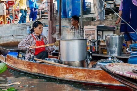 thai fruit: Damnoen Saduak, Thailand - February 2, 2009: Thai woman prepares food in a boat at the Floating Market in Damnoen Saduak. The floating market is a major tourist attraction.