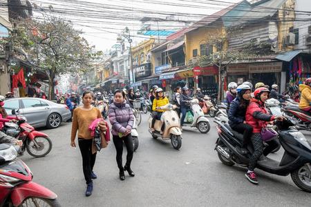 Hanoi, Vietnam - Februari 10, 2015: De Vietnamese vrouwen kruisen de straat door bezig verkeer in het oude kwart van Hanoi. Er zijn ongeveer vier miljoen motorfietsen in de straten van Hanoi. Redactioneel
