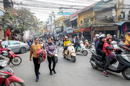 Hanoi, Vietnam - February 10, 2015: Vietnamese women cross the street through busy traffic in the old quarter of Hanoi. There are approximately four million motorbikes on the streets of Hanoi.
