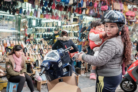 guilds: Hanoi, Vietnam - February 10, 2015: Vietnamese woman with a child shopping in the old quarter of Hanoi. The 36 old streets and guilds of the old quarter are a major tourist attraction.
