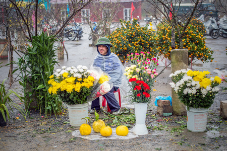 rugged man: Sapa, Vietnam - February 13, 2015: Vietnamese man selling flowers on a rainy day at the market in Sapa. Sapa is famous for its rugged scenery and its cultural diversity. Editorial
