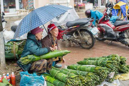 diversidad cultural: Sapa, Vietnam - 13 de febrero 2015: las mujeres de Red Dao vender bajo un paraguas en un d�a lluvioso en el mercado de Sapa. Sapa es famosa por su paisaje agreste y su diversidad cultural.
