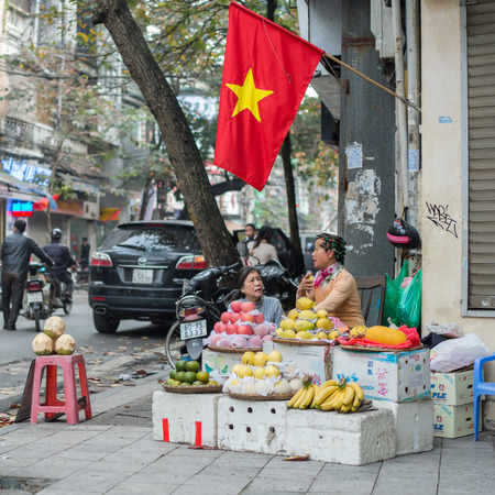 guilds: Hanoi, Vietnam - February 15, 2015:  Vietnamese women selling fruits in the old quarter of Hanoi. The 36 old streets and guilds of the old quarter are a major tourist attraction.