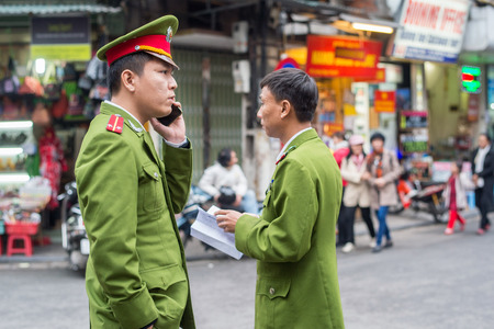 Hanoi, Vietnam - February 11, 2015: Police men on patrol in the old quarter of Hanoi. The 36 old streets and guilds of the old quarter are a major tourist attraction.