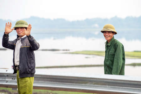 exporter: Lao Cai, Vietnam - February 12, 2015: Cheerful road workers with rice fields in the background outside Lao Cai. Vietnam is the second largest exporter of rice worldwide.