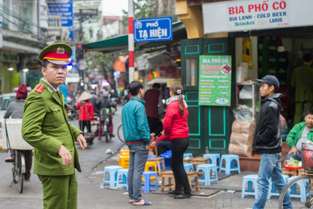 guilds: Hanoi, Vietnam - February 11, 2015:  Vietnamese policeman patrolling in the old quarter of Hanoi. The 36 old streets and guilds of the old quarter are a major tourist attraction.
