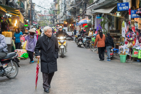 Hanoi, Vietnam - February 11, 2015:  Stylish elderly Vietnamese man walking in the old quarter of Hanoi. The 36 old streets and guilds of the old quarter are a major tourist attraction. Editorial