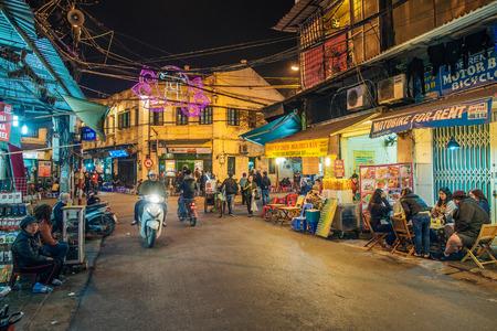 Hanoi, Vietnam - 11 februari 2015: Motorbike verkeer 's nachts in de oude wijk van Hanoi. De 36 oude straatjes en gilden van de oude wijk zijn een belangrijke toeristische attractie.