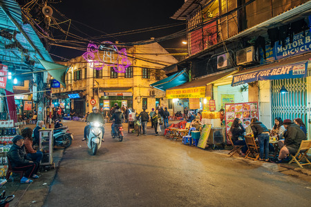 Hanoi, Vietnam - February 11, 2015:  Motorbike traffic by night in the old quarter of Hanoi. The 36 old streets and guilds of the old quarter are a major tourist attraction.