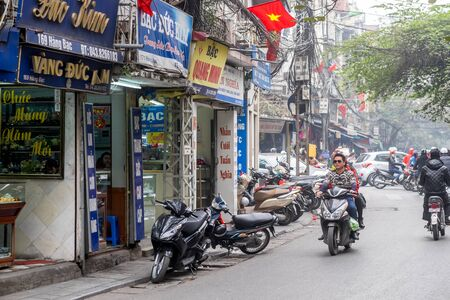 guilds: Hanoi, Vietnam - February 10, 2015:  Motorbike traffic in the old quarter of Hanoi. The 36 old streets and guilds of the old quarter are a major tourist attraction. Editorial