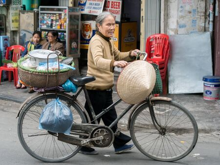 guilds: Hanoi, Vietnam - February 10, 2015: Vietnamese woman walks with a bike in the old quarter of Hanoi. The 36 old streets and guilds of the old quarter are a major tourist attraction. Editorial