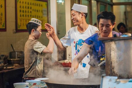 muslim: Xian China  July 3 2012: Hui muslims prepare street food at famous Muslim Street in Xian. Hui people are a Muslim ethnic minority in Xian and run a lively market at Muslim Street. Editorial
