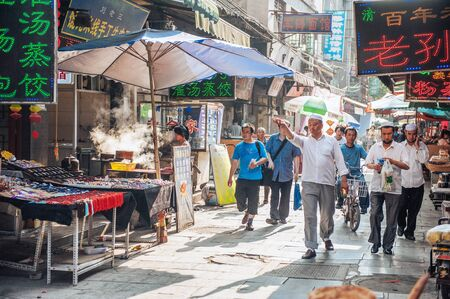 stroll: Xian China  June 20 2012: Chinese tourists and Hui people stroll at famous Muslim Street in Xian. Hui people are a Muslim ethnic minority in Xian and run a lively market at Muslim Street.