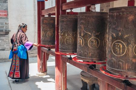 Provincie Qinghai, China 25 juni 2012: Tibetaanse vrouw bidden op Kumbum klooster. Dit Tibetaans Boeddhistisch klooster gesticht door de derde Dalai Lama in 1583 op de tweede plaats alleen naar Lhasa in belang toe. Redactioneel