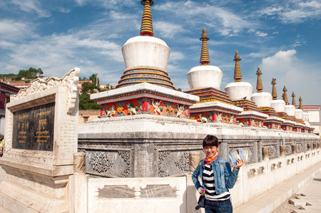 dalai: Qinghai Province, China  June 25, 2012: Chinese tourist in front of the famous eight pagodas at Kumbum Monastery. This Tibetan Buddhist monastery founded by the third Dalai Lama in 1583 ranks second only to Lhasa in importance. Editorial